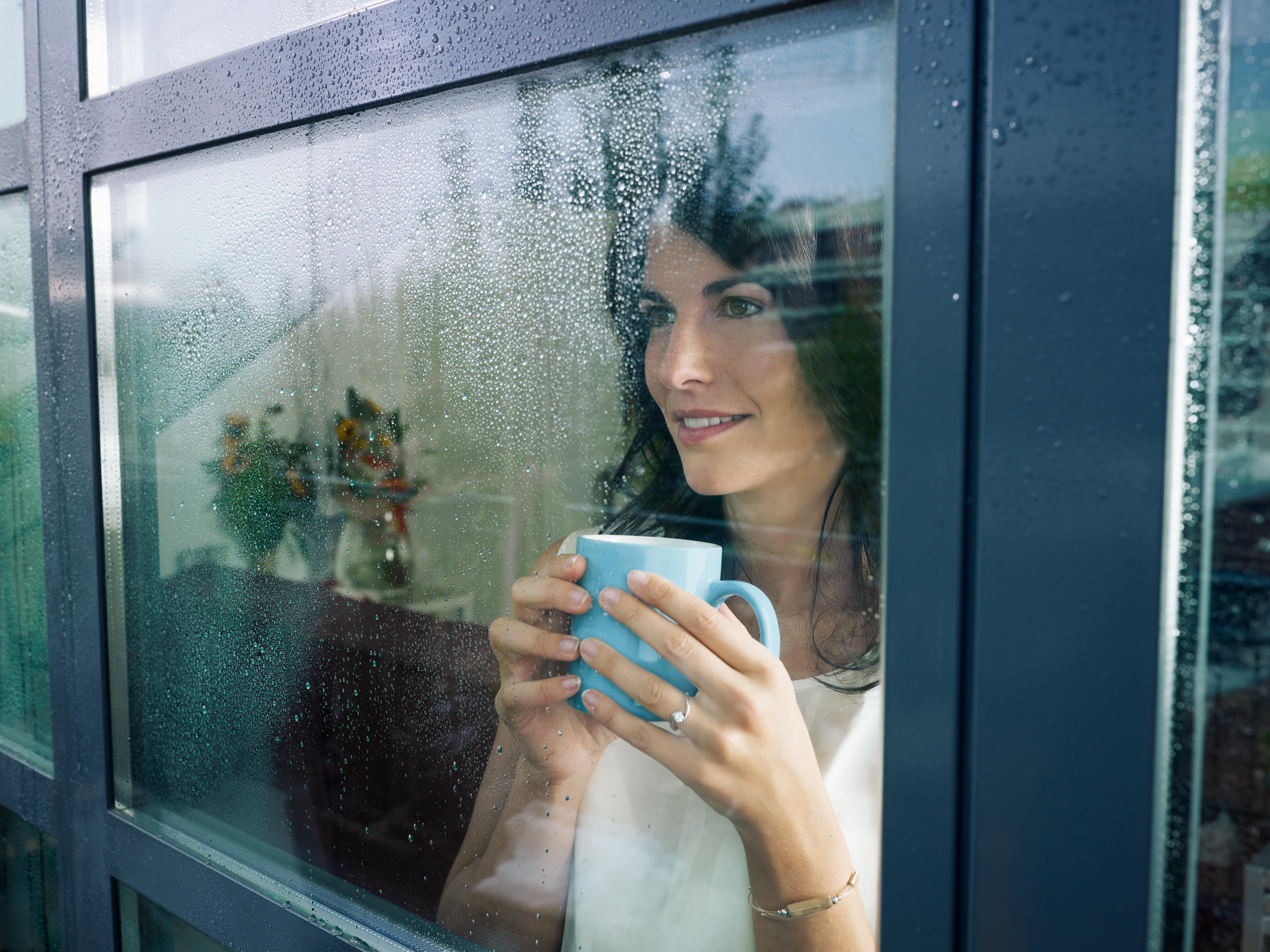 Une femme reposée, pensant devant sa fenetre PVC Oknoplast